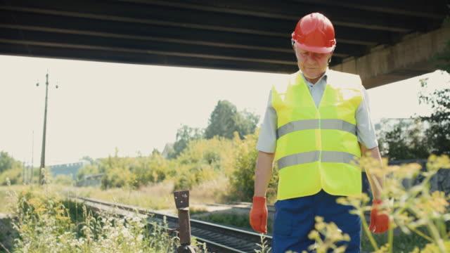 Senior engineer in uniform and helmet looking thoughtfully on the railways video