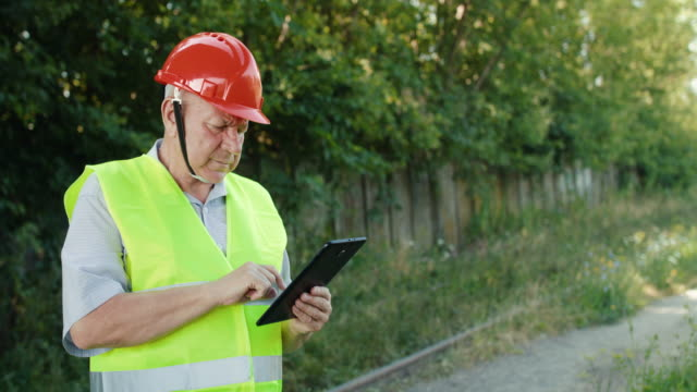 Senior engineer in uniform fixing data on the tablet outdoors in summer video