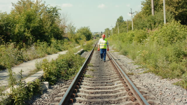A senior engineer in uniform walks along the track to check it in summer day video