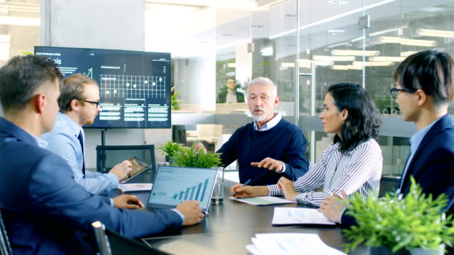 vídeos de stock e filmes b-roll de senior executive explains company's vision and potential to his employees. they are sitting at big table in meeting room. tv screen on the wall shows corporate growth. - senior business woman tablet