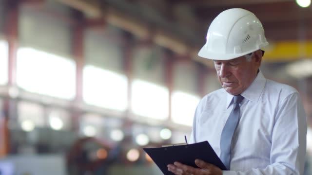 senior facility manager observing working process - ispettore della qualità video stock e b–roll