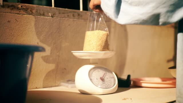 Senior farmer hands weighing the brown rice on the kilogram weight meter in the household.