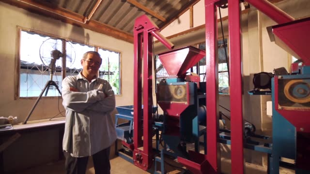 Senior farmer with arms crossed standing beside a rice milling machine in the household. LS Dolly right Camera and selective focus with color grading. Use for background clip or insert shot of Senior farmer with arms crossed standing beside a rice milling machine in the household. rice cereal plant stock videos & royalty-free footage
