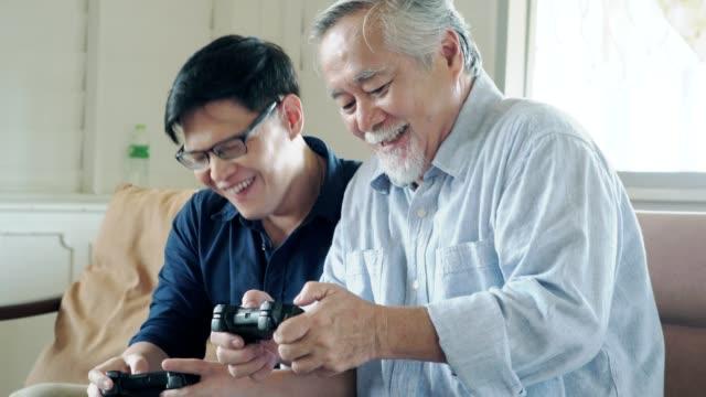 先輩の父親と彼の大人の息子は一緒にビデオゲームを楽しんでいます。 - disruptagingcollection点の映像素材/bロール