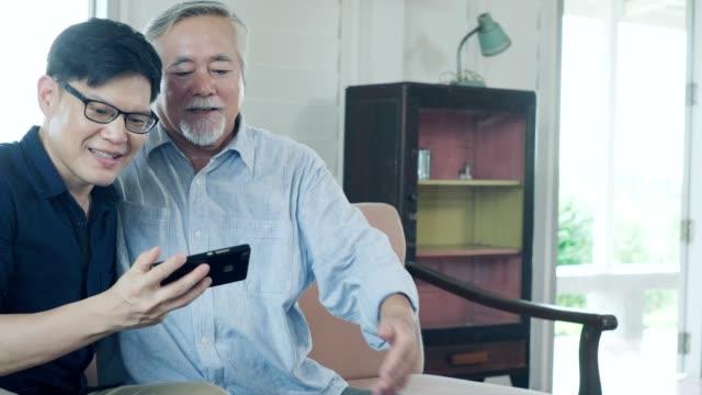 先輩の父親と彼の大人の息子は家にいる間一緒に時間を過ごします。 - disruptagingcollection点の映像素材/bロール