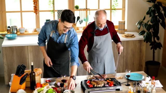 il padre anziano che dà al suo giovane figlio consigli sui trucchi di cucina - padre single video stock e b–roll
