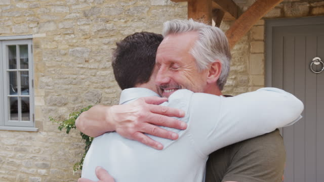 Senior Father Greets And Hugs Adult Son Outside Door Of House As He Visits – Video