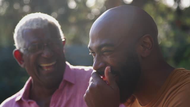 stockvideo's en b-roll-footage met hogere vader die en met volwassen zoon in tuin thuis spreekt spreekt lacht - lachen