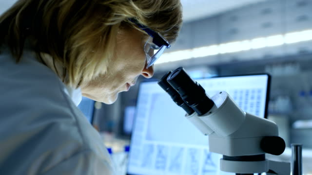 Senior Female Biologist Works on Her Computer and Looks at Materials under Microscope. She's in a Modern Laboratory. Senior Female Biologist Works on Her Computer and Looks at Materials under Microscope. She's in a Modern Laboratory. Shot on RED EPIC-W 8K Helium Cinema Camera. microscope stock videos & royalty-free footage