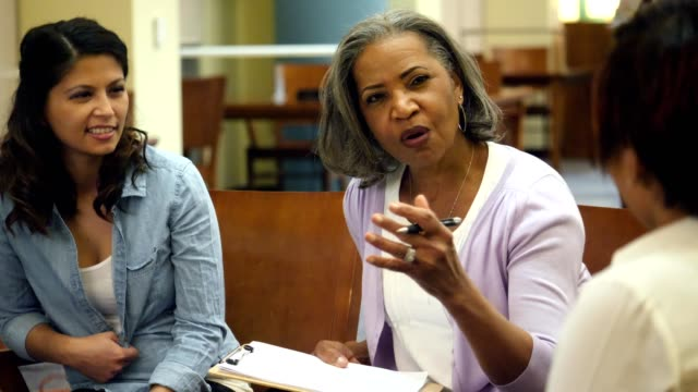 Senior female college professor discusses something with adult students Beautiful senior African American college professor meets with a group of students pursuing an advanced degree. She gestures while explaining something to the students. mid adult stock videos & royalty-free footage