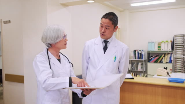 東京病院の先輩女性医師と男性同僚 - 聴診器点の映像素材/bロール