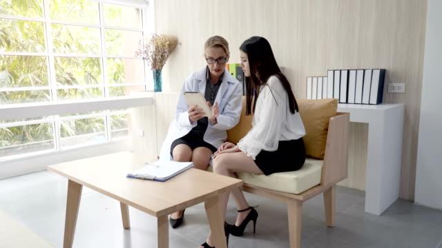 先輩女性医師は、患者にタブレットの情報を使って何かを説明しています。 ビデオ