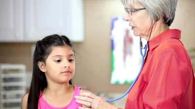 Senior Female doctor, Latin descent female patients in pediatrician's office. video