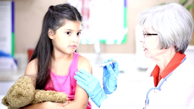 Senior Female doctor, Latin descent female patients in pediatrician's office.  We also have photos from this shoot. Studio shot of two Latin descent girls visiting the doctor for flu shots and check ups.  The Doctor is a Senior Woman. This is a real Latin family. The little girl is smiling holding her teddy bear while getting a flu shot. The doctor is wearing a lab coat.  We also have photos from this shoot. flu shot stock videos & royalty-free footage