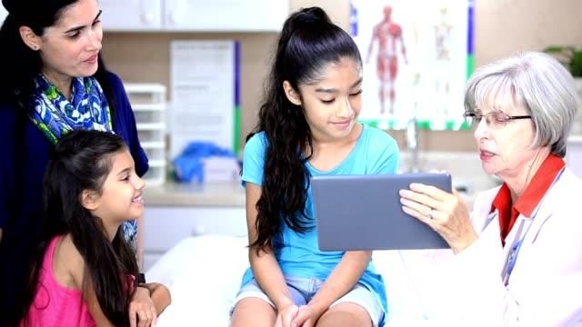 vídeos y material grabado en eventos de stock de senior femenino médico, pacientes femeninos de ascendencia latina en la oficina del pediatra.  también tenemos fotos de esta sesión. - pediatra