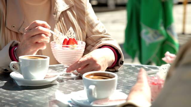 Senior Female Friends Eating Dessert At Outdoor Cafe video