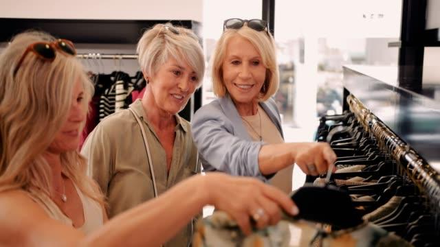 amiche senior che si divertono a fare shopping insieme nel negozio di abbigliamento - donne mature video stock e b–roll