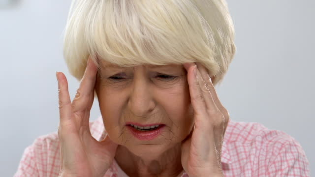 Senior female massaging temple, suffering from head ache, health disorder Senior female massaging temple, suffering from head ache, health disorder painkiller stock videos & royalty-free footage