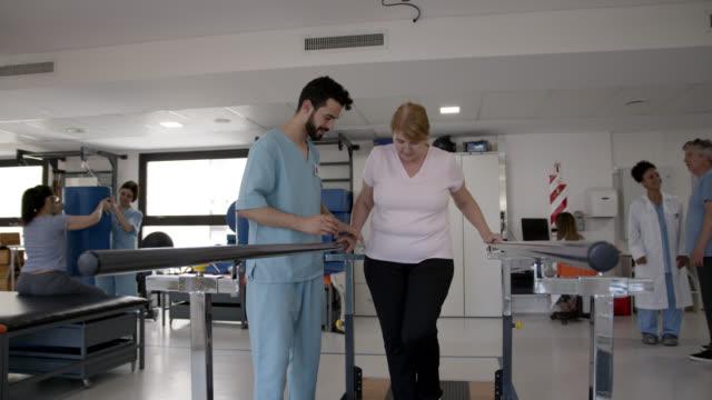 治療中に平行棒のサポートと歩く彼女の男性セラピストによって支援されたシニア女性患者 - 医療スクラブ点の映像素材/bロール