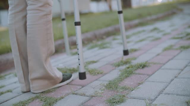 公共公園でモビリティウォーカーを使用するシニア女性患者 - 介護点の映像素材/bロール