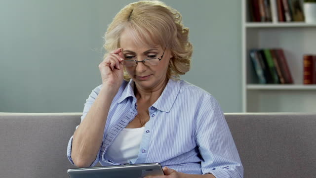 Senior female putting on glasses and looking at tablet, reading online newspaper video