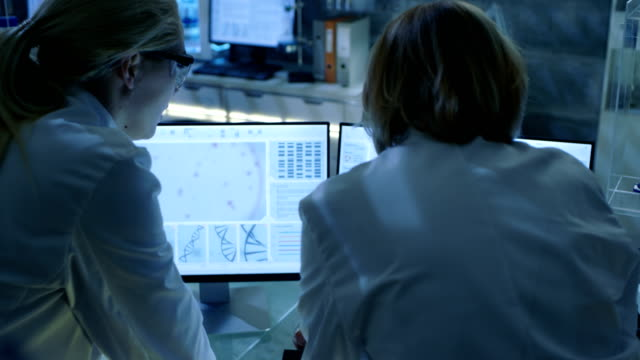 Senior Female Scientist Discusses Scientific Data with Her Laboratory Assistant. They're looking at Two Displays in a Modern Laboratory. video
