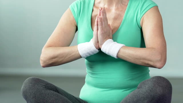 Senior female sitting in lotus position, putting palms together, doing yoga video