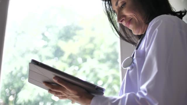senior kvinna kvinna läkare använder tabletpc, slow motion - anteckningsblock bildbanksvideor och videomaterial från bakom kulisserna