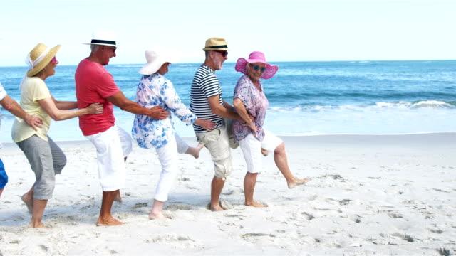 Sênior amigos dançando na praia - vídeo