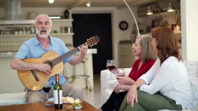 senior friends har en drink hemma - akustisk gitarr bildbanksvideor och videomaterial från bakom kulisserna
