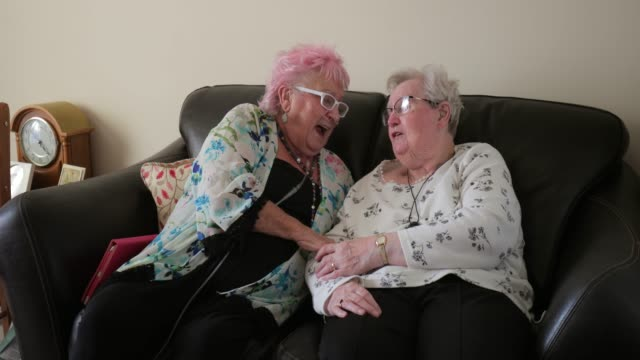 Senior Friends Having a Good Laugh Two senior woman sitting chatting in a nursing home in North East of England. One has pink hair. They are sitting on a sofa having a good laugh. One woman is wearing a nasal oxygen cannula. Another lady has a personal alarm GPS tracker around her neck. medical oxygen equipment stock videos & royalty-free footage