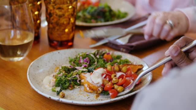 seniora vänner har vegansk mat vid matbordet - hälsosamt ätande bildbanksvideor och videomaterial från bakom kulisserna