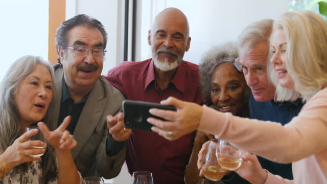 Senior friends looking at smart phone in party Handheld shot of retired friends watching video on smart phone. Senior men and women talking while enjoying drinks together. They are wearing casuals in party at home. mixed race person stock videos & royalty-free footage