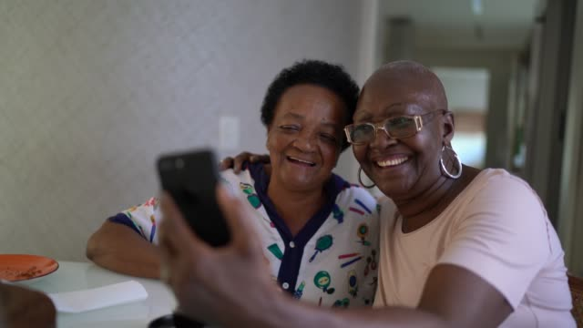 Senior friends women doing a video call using smartphone Senior friends women doing a video call using smartphone zoom call stock videos & royalty-free footage