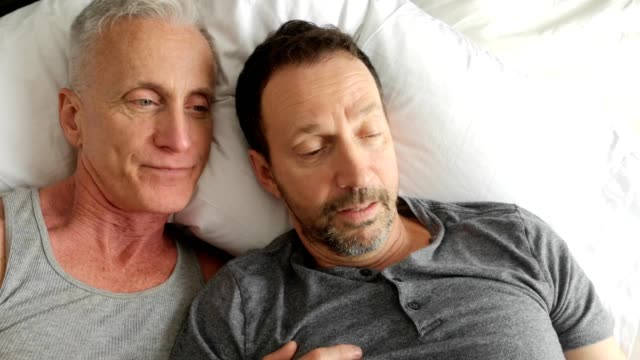 Senior gay couple having fun with mobile phone while in bed together