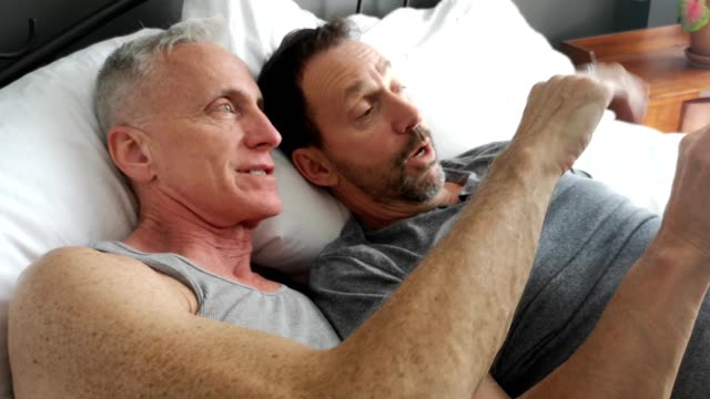 Senior gay couple interacting with phone while in bed together