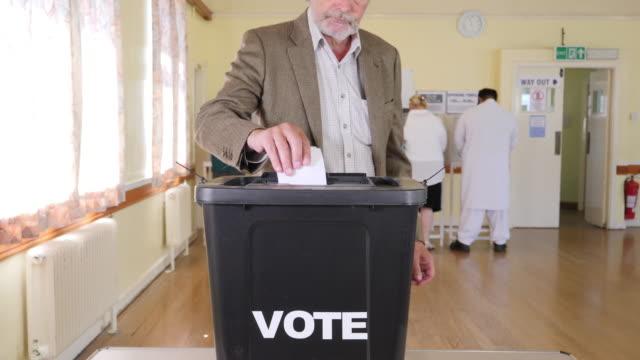 vídeos y material grabado en eventos de stock de 4k: senior caballero poner voto en urna en las elecciones - voto en colegio electoral - polling place