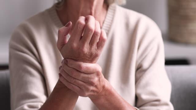 vídeos de stock e filmes b-roll de senior grandmother massaging hand suffering from rheumatoid arthritis - membro