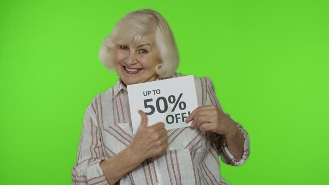 старшая бабушка показывает до 50 процентов off надпись, рекламные скидки, глядя поражен - cyber monday стоковые видео и кадры b-roll