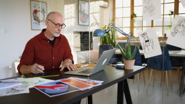 Senior graphic designer working in his home office video