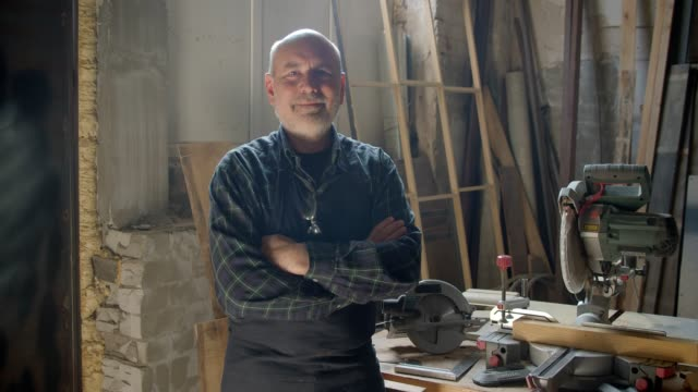 Senior gray haired male carpenter standing at wood manufacture with crossed arms smiling positively into camera.