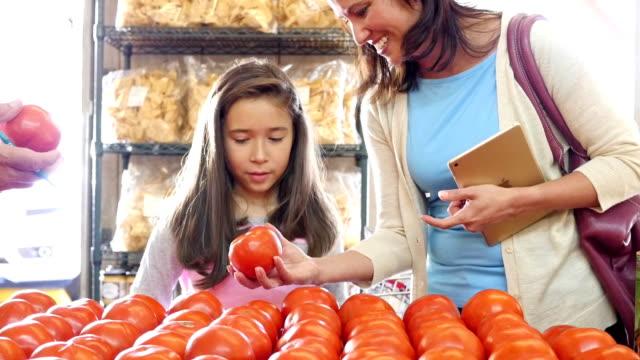 старший бакалейщик помогает латиноамериканцы мать и дочь подобрать помидоры на рынке производства - томат овощ стоковые видео и кадры b-roll