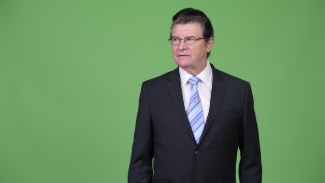 äldre stilig affärsman som pekar åt sidan - kostym sida bildbanksvideor och videomaterial från bakom kulisserna