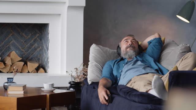 vidéos et rushes de senior ayant des loisirs tout en appréciant la musique à la maison - podcasting