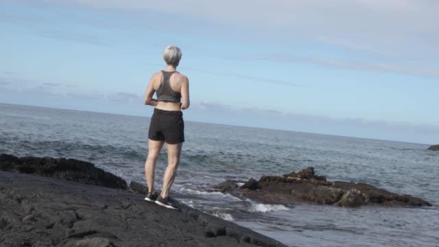 Senior hiking and looking at ocean waves