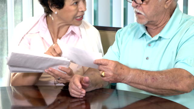 Senior Hispanic couple looking through bills A senior hispanic couple sitting at home at a table by a window, looking worried as they discuss a stack of bills to be paid. The woman is in her 60s and her husband is in his 80s. face to face stock videos & royalty-free footage