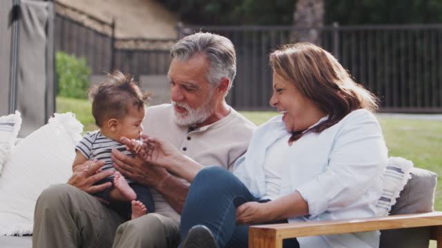 coppia ispanica anziana seduta su un sedile in giardino con il loro nipotino, da vicino - etnia latino americana video stock e b–roll