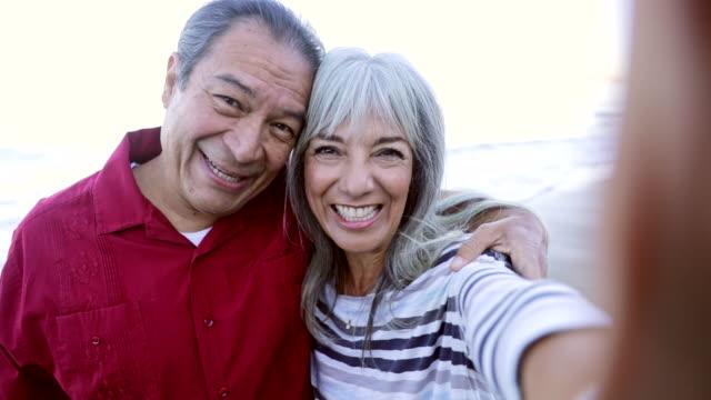 starsza para latynoska robiąca selfie na plaży - aktywny tryb życia filmów i materiałów b-roll