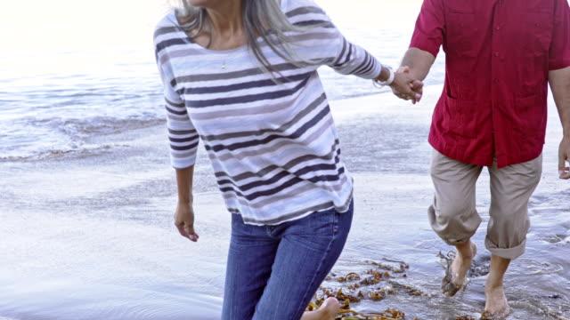 coppia ispanica senior che cammina lungo la spiaggia - etnia video stock e b–roll