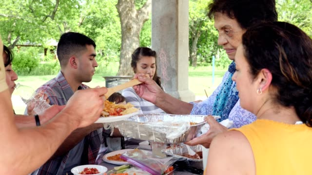 Senior Hispanic grandmother serves her family a delicious meal